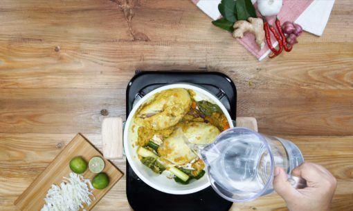Menambahkan air ke dalam panci berisi bumbu soto ayam sambal matah.