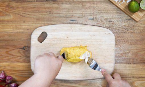 Menyuwir ayam di atas talenan dengan menggunakan garpu untuk resep soto ayam sambal matah.