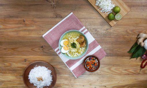 Soto ayam sambal matah telah matang dan disajikan dalam mangkuk dengan didampingi nasi putih hangat.