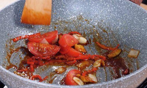 Menambahkan tomat ke dalam tumisan bahan ayam kecap.