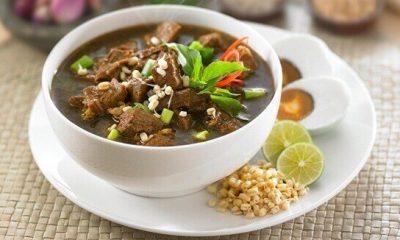 Hasil masak resep rawon daging sapi tersaji di dalam mangkuk beserta telur asin.