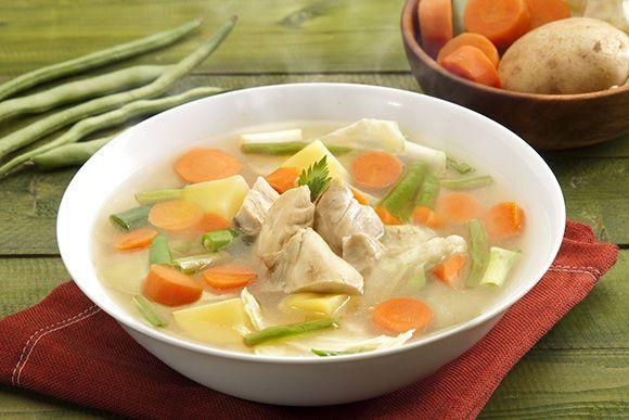 Mangkuk berisi sup ayam bening dengan sayuran berupa wortel, kentang, dan buncis.