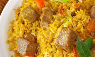 Hasil memasak resep nasi goreng kambing kebuli tersaji di atas piring putih.