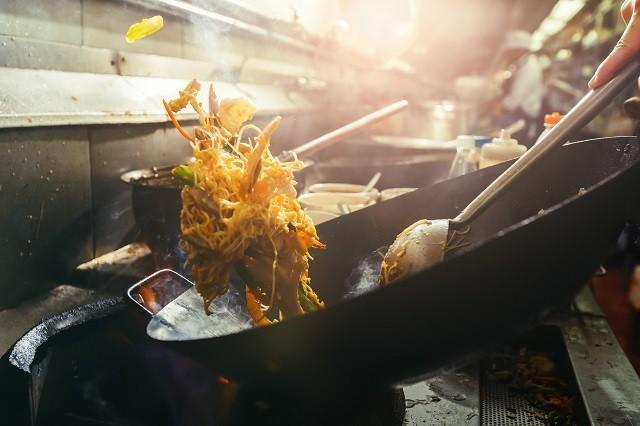 Chef menggunakan wok untuk resep masakan Cina seperti mi goreng