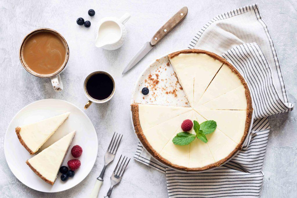 Cheese cake khas Amerika difoto vertikal bersama secangkir kopi.