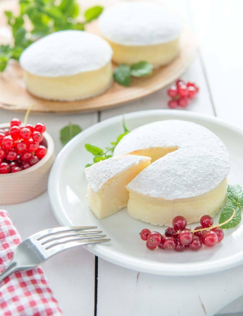 Cheese cake khas Jepang tersaji di atas piring putih dan buah-buahan.