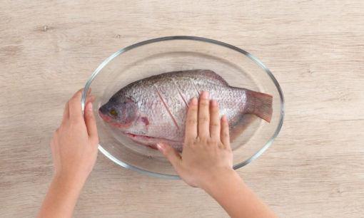Membumbui ikan untuk resep ikan goreng acar kuning.
