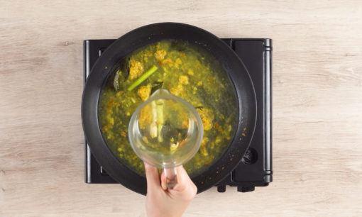 Menuangkan air pada bumbu yang tengah dimasak untuk resep ikan goreng acar kuning.