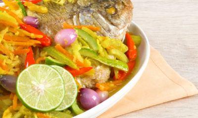 ikan goreng acar kuning tersaji di atas piring putih.