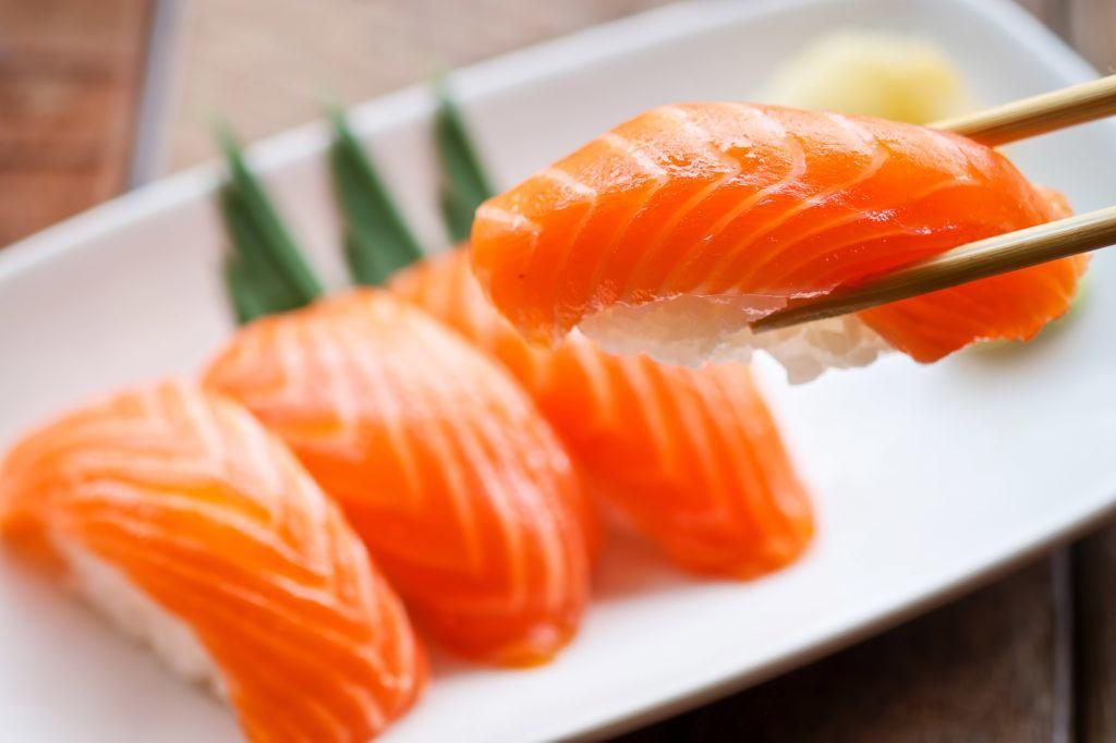 Sushi ikan salmon disumpit.