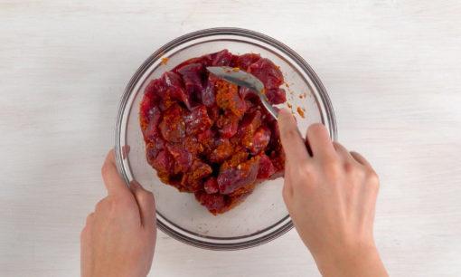 Mengaduk rata bumbu halus bersama daging untuk sate rembiga.