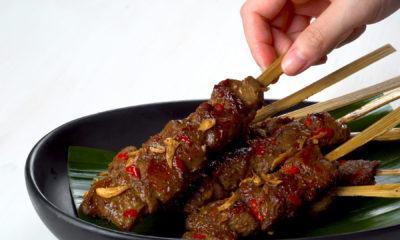 Sate rembiga khas Lombok tersaji di atas piring hitam.