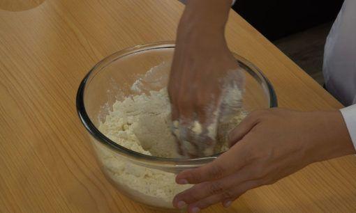 Melubangi bagian tengah adonan sebagai bagian dari cara membuat donat.