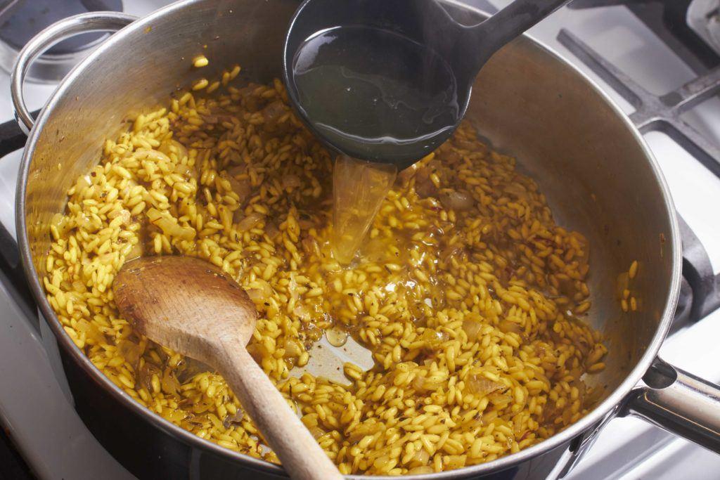 Cara membuat risotto adalah menuangkan kaldu ayam ke dalam panci berisi nasi.