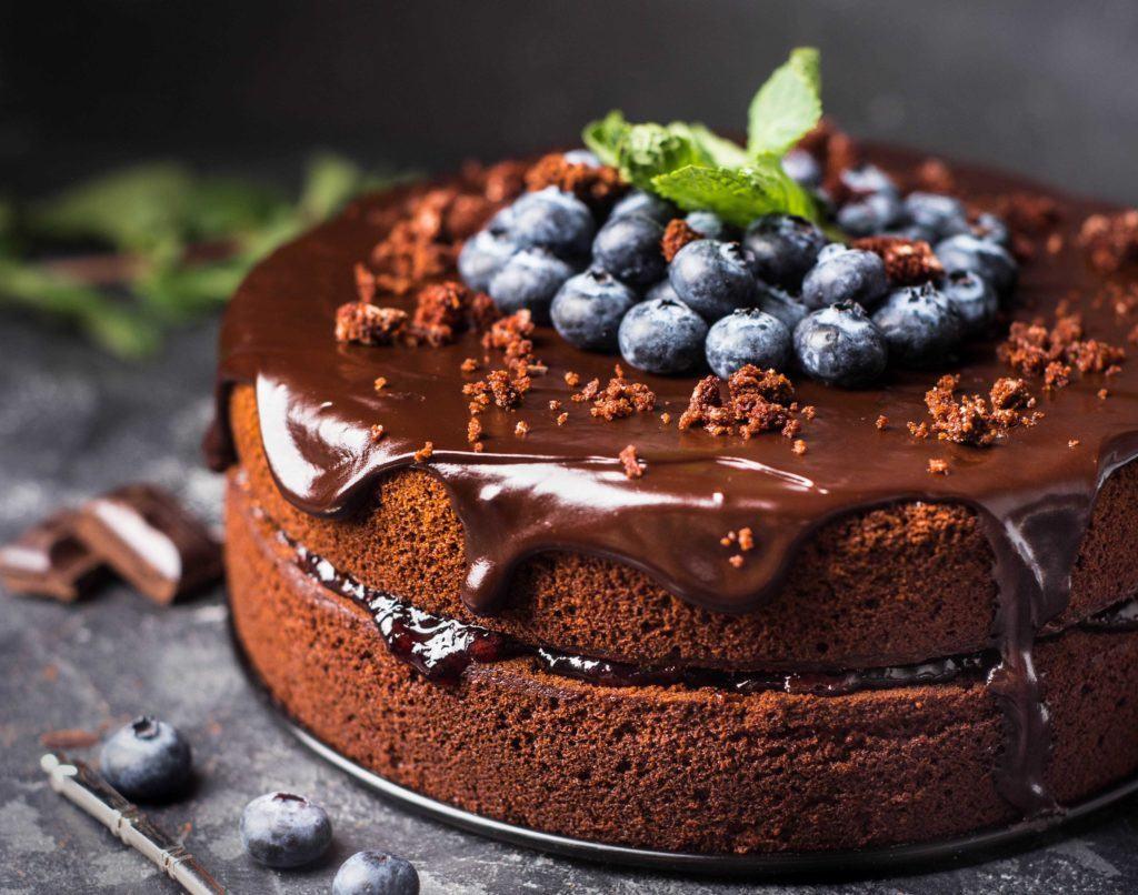 Makanan manis dalam bentuk chocolate cake dengan buah.