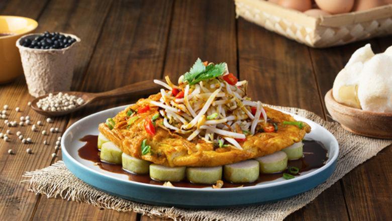 Tahu tek telur Surabaya tersaji di atas piring dan lontong.