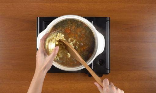 Menambahkan sayuran ke dalam kuah sup tomat.