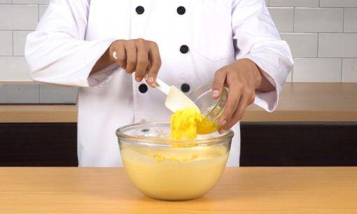 Mencampur margarin dan adonan untuk cara membuat bolu kukus keju.