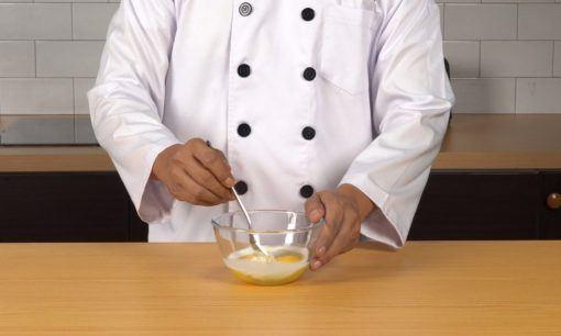 Mencampurkan susu dan telur untuk cara membuat nugget ikan.