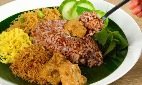 Nasi Ulam Betawi disajikan di atas piring.