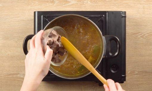 Menambahkan daging ke kuah untuk resep Tahu Campur.
