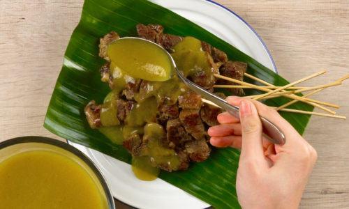 Membubuhi kuah sate Padang.