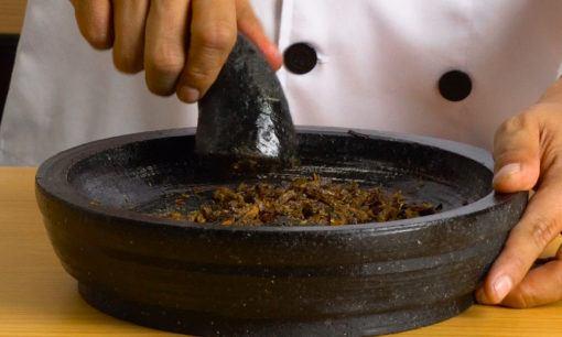 Menggiling ikan untuk sambal roa.