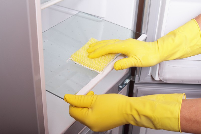 Cara membersihkan bagian rak kulkas.