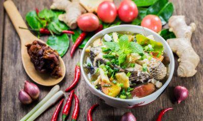 Sup ikan asam pedas dengan taburan daun aromatik.