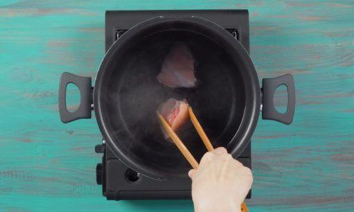 Merebus ayam untuk resep soto ayam bihun.