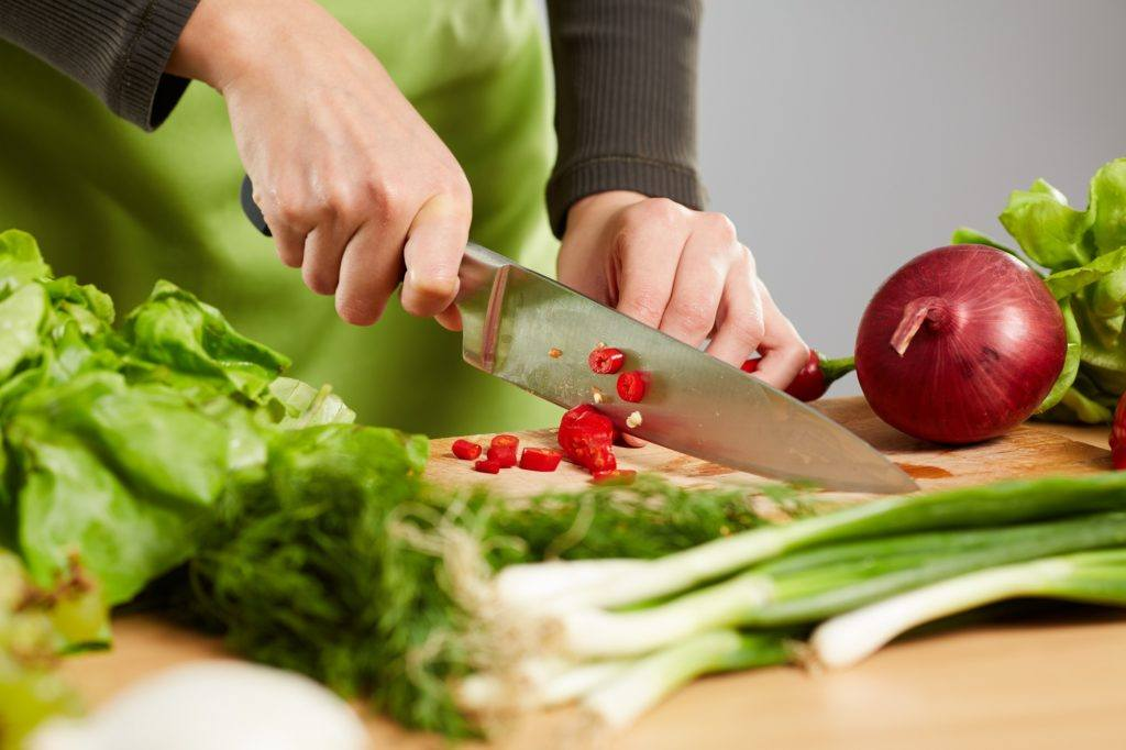 Seorang wanita mengiris cabai dan sayuran dengan pisau dapur.