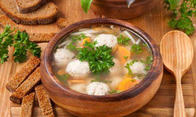 Sup tahu bakso ikan hangat disajikan di dalam mangkuk kayu.
