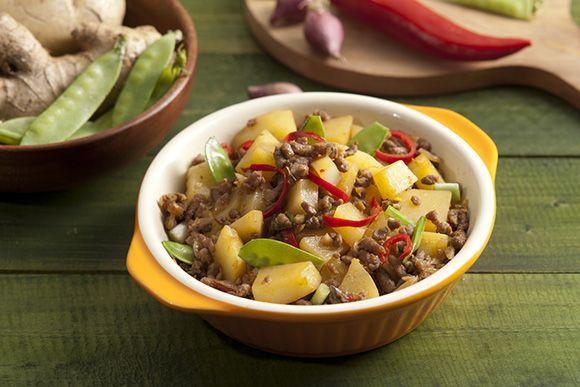 Mangkuk berisi tumis kentang ayam cincang tersaji di atas meja kayu dan didampingi kacang kapri.