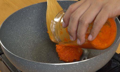 Tangan chef sedang memasukkan bumbu untuk ditumis.