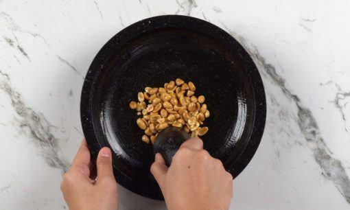 Menumbuk kacang untuk resep salad sayur.