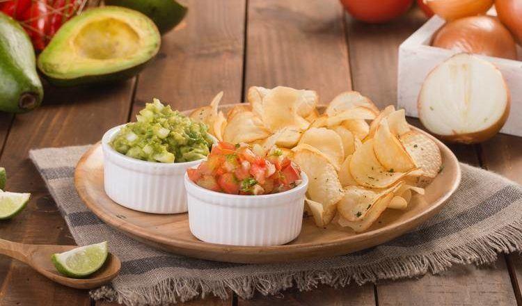 Sepiring keripik singkong disajikan dengan saus salsa