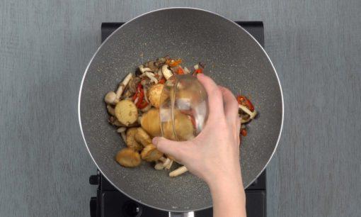 tofu yang telah digoreng dituangkan ke dalam tumisan jamur dalam wajan