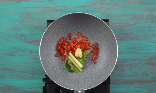 potongan cabai, sereh, dan bawang putih ditumis dalam wajan.