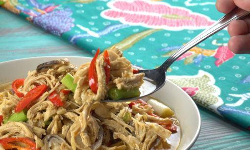 Semangkuk semur ayam suwir jamur tampil dengan taplak batik.