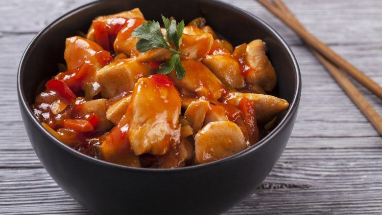 Hasil masak resep ayam pedas saus merah berlatar kayu.