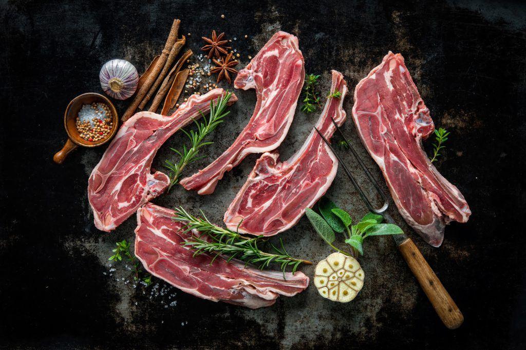 Mengolah daging kambing dengan latar belakang batu dan garpu besar.