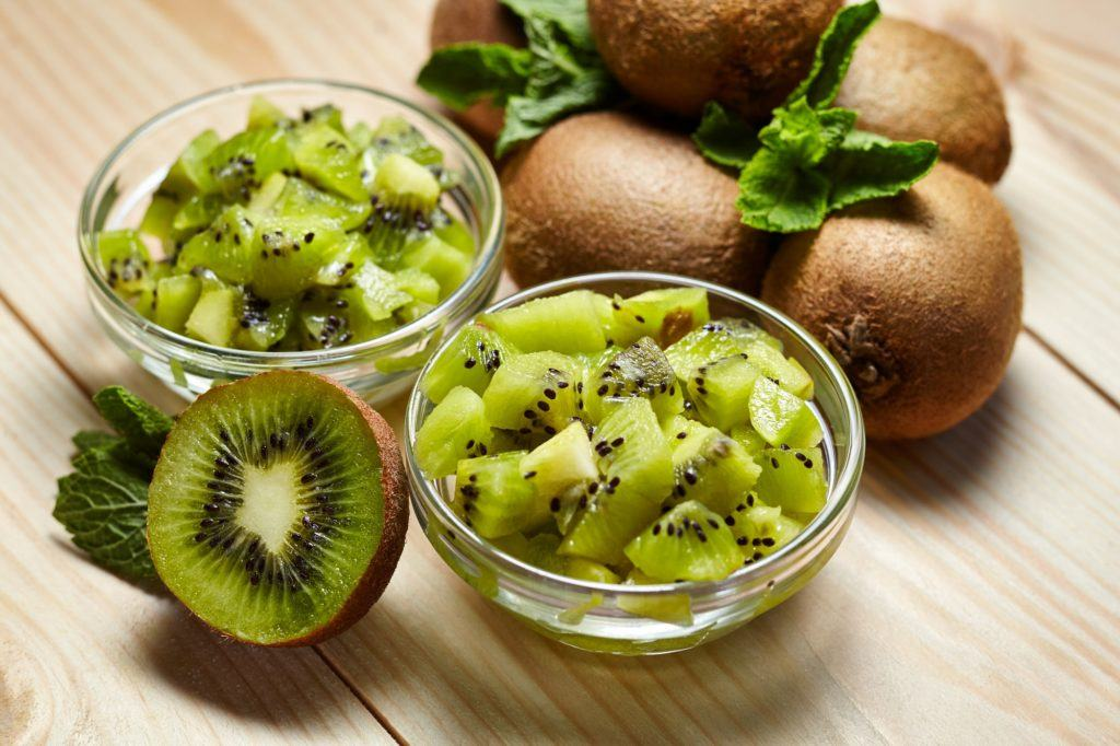 Potongan kiwi di dalam dua mangkuk dengan beberapa kiwi yang belum dikupas di belakangnya.