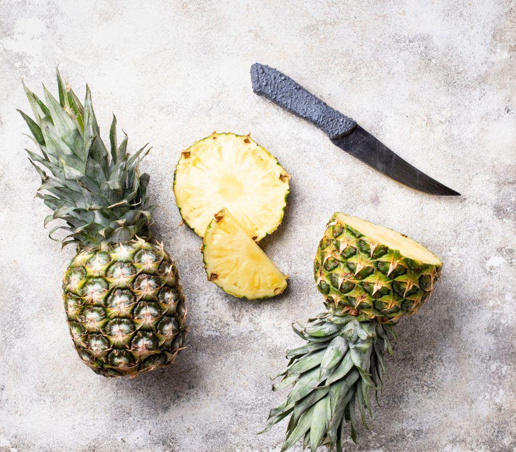 dua buah nanas, salah satunya dipotong dan pisau di sampingnya