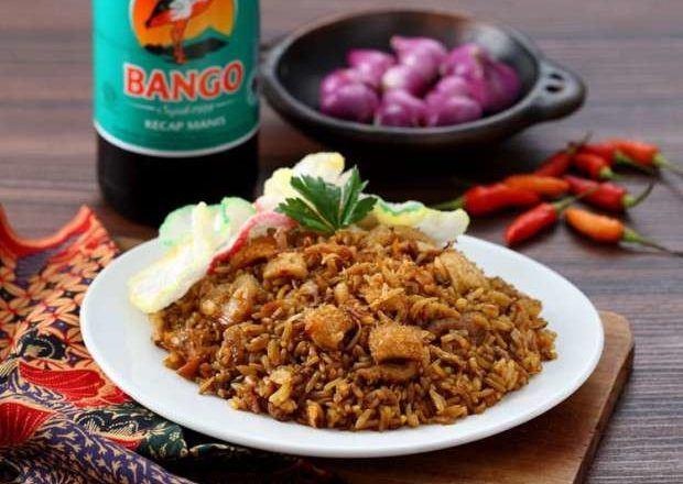 Satu piring nasi goreng babat gongso di atas talenan. Di belakangnya ada kecap bango, bawang merah, dan cabai.