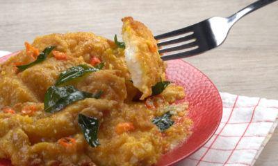 Ikan dori salted egg tersaji di atas piring merah dan tengah dinikmati.