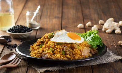Satu piring nasi goreng bumbu opor di atas piring berwarna hitam.