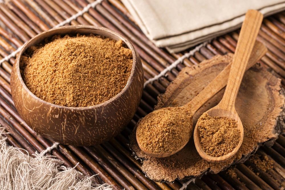Gula kelapa bubuk tersaji di atas mangkuk dan sendok kayu.