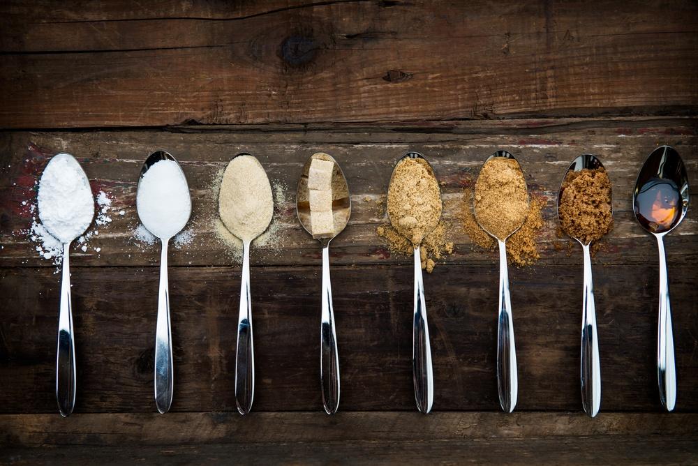 Beberapa sendok dengan isian bahan pengganti gula diletaakkan berjajar di atas meja.