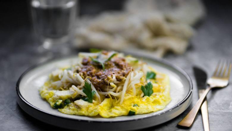 Tahu telur bumbu kacang tersaji bersama alat makan dan gelas.