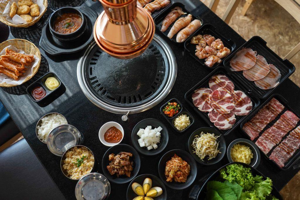 Meja berisi panggangan dan bahan-bahan Korean BBQ.